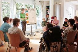 Stuhlkreis, bei dem eine Frau etwas an einer Flip Chart Tafel erklärt