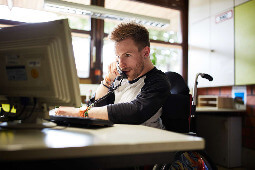 Junger Mann, der am Computer sitzt und telefoniert