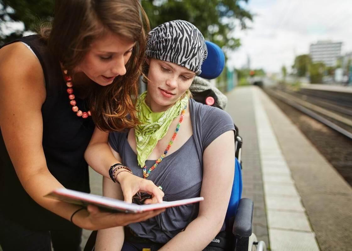 Frau im Rollstuhl, die etwas in einem Buch erklärt bekommt