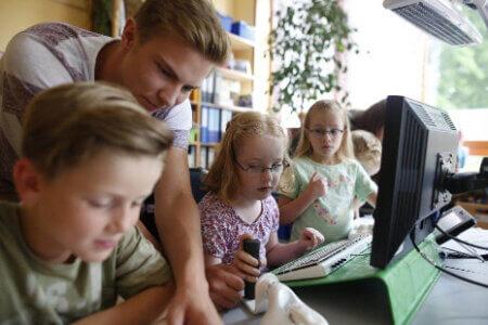 Kinder, die auf der Schulbank sitzen und etwas erklärt kriegen