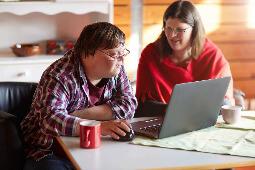 Zwei Menschen, die gemeinsam am Computer sitzen