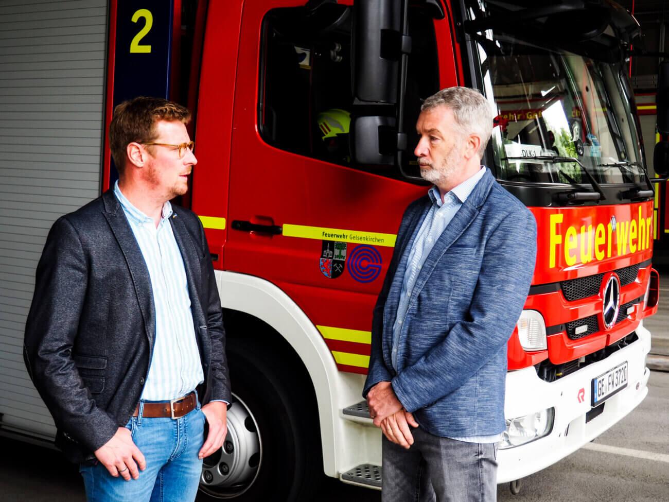 Julius Leberl und Frank Flieger stehen vor einem Feuerwehrauto und reden über Inklusion